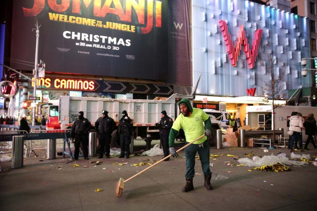 A New York City Department of Sanitation worker cleans the streets after the New Year celebrations in Times Square in Manhattan, New York, U.S., January 1, 2018. REUTERS/Amr Alfiky