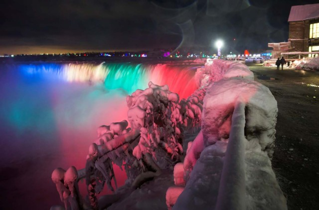 Visitors walk near the brink of the ice covered Horseshoe Falls in Niagara Falls, Ontario, Canada, January 2, 2018. REUTERS/Aaron Lynett