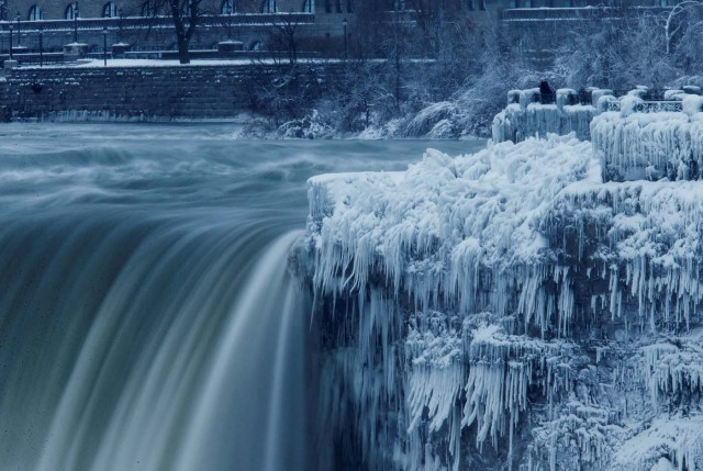 A lone visitor takes a picture near the brink of the ice covered Horseshoe Falls in Niagara Falls, Ontario, Canada, January 3, 2018. REUTERS/Aaron Lynett