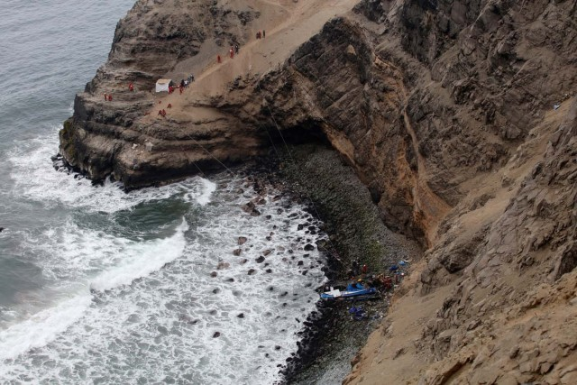 Rescue workers work at the scene after a bus crashed with a truck and careened off a cliff along a sharply curving highway north of Lima, Peru, January 3, 2018. REUTERS/Guadalupe Pardo