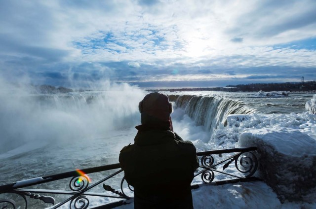 A visitor takes pictures near the brink of the ice covered Horseshoe Falls in Niagara Falls, Ontario, Canada, January 3, 2018. REUTERS/Aaron Lynett