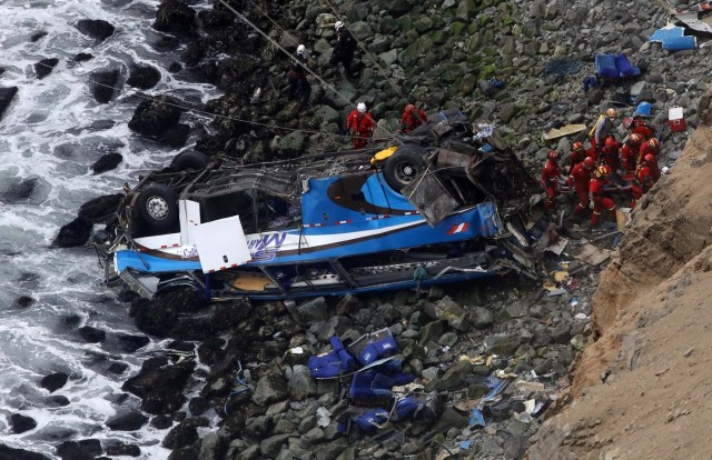 Rescue workers work at the scene after a bus crashed with a truck and careened off a cliff along a sharply curving highway north of Lima, Peru, January 3, 2018. REUTERS/Guadalupe Pardo TPX IMAGES OF THE DAY