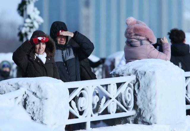 Visitors watch the ice covered Horseshoe Falls in Niagara Falls, Ontario, Canada, January 3, 2018. REUTERS/Aaron Lynett