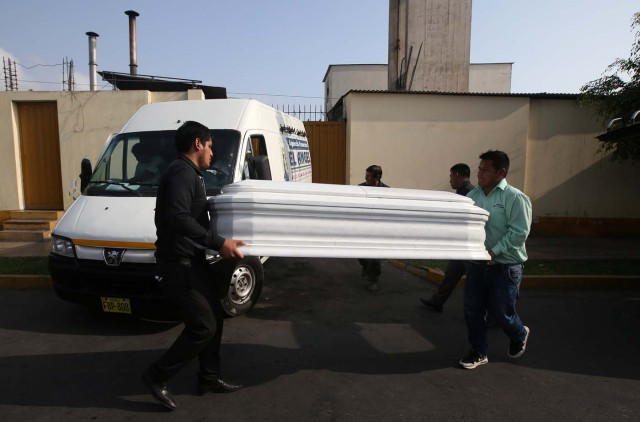 People carry coffins for the victims of a bus that crashed with a truck and careened off a cliff along a sharply curving highway north of Lima, wait outside a hospital morgue in Chancay, Peru, January 3, 2018. REUTERS/Guadalupe Pardo
