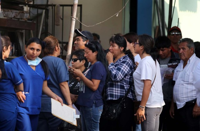 Relatives of the victims of a bus that crashed with a truck and careened off a cliff along a sharply curving highway north of Lima, wait outside a hospital morgue in Chancay, Peru, January 3, 2018. REUTERS/Guadalupe Pardo