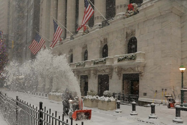 A worker clears snow from the front of the New York Stock Exchange during a snowstorm in New York, U.S., January 4, 2018. REUTERS/Lucas Jackson