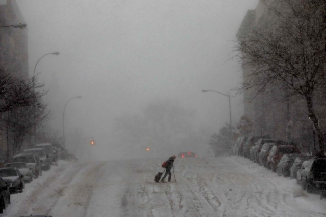 A woman struggles across a snow-covered 145th Street in upper Manhattan during a snowstorm in New York City, New York, U.S., January 4, 2018. REUTERS/Mike Segar