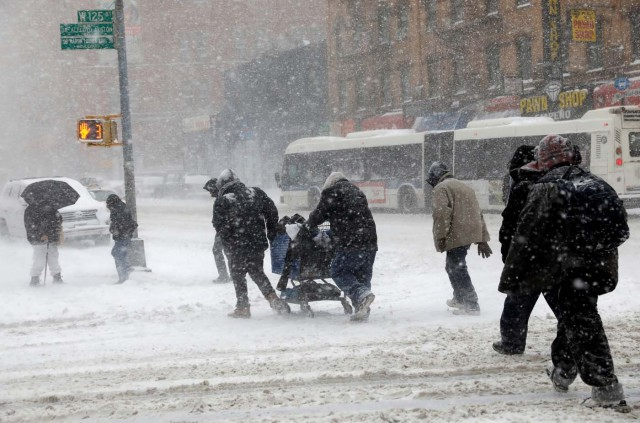 People struggle against wind and snow as they cross 125th street in upper Manhattan during a snowstorm in New York City, New York, U.S., January 4, 2018. REUTERS/Mike Segar