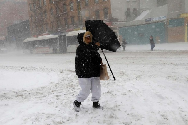 A woman struggles against wind and snow as she crosses 125th street in upper Manhattan during a snowstorm in New York City, New York, U.S., January 4, 2018. REUTERS/Mike Segar