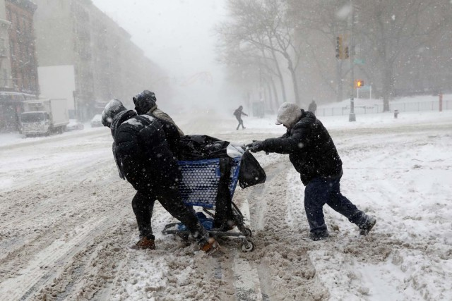 Men struggle against wind and snow as they push a shopping cart across 125th street in upper Manhattan during a snowstorm in New York City, New York, U.S., January 4, 2018. REUTERS/Mike Segar