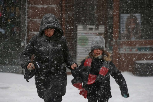 People struggle against wind and snow during a snowstorm in the Brooklyn borough of New York City, U.S., January 4, 2018. REUTERS/Brendan McDermid