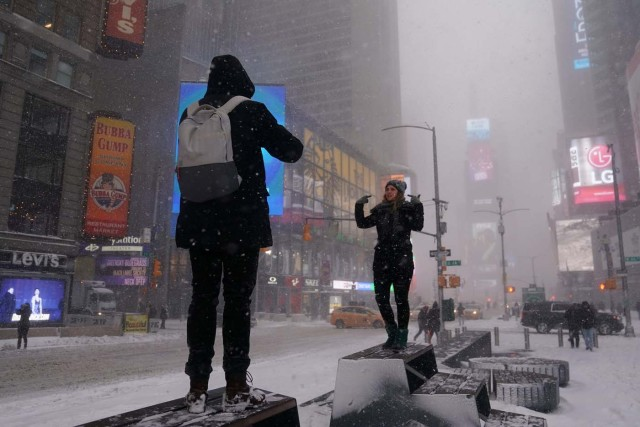 People take photos in Times Square during a snowstorm in New York City, New York, U.S., January 4, 2018. REUTERS/Carlo Allegri