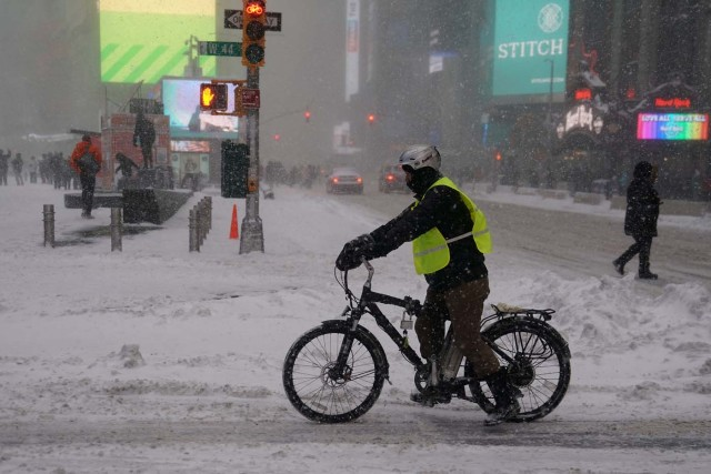 A delivery person on a bicycle makes his way though Times Square during Storm Grayson in New York City, New York, U.S., January 4, 2018. REUTERS/Carlo Allegri