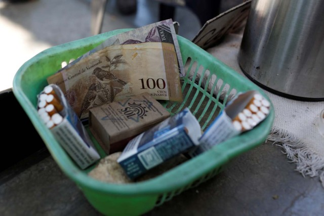 Venezuelan bolivar notes and cigarettes on sale are seen in a basket in downtown Caracas, Venezuela