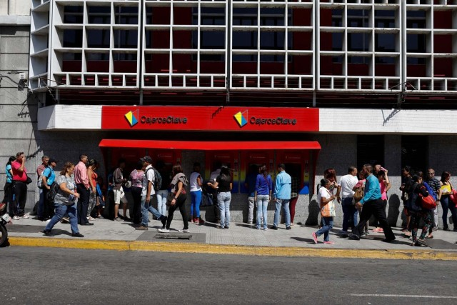 People line up to withdraw cash from an automated teller machine (ATM) outside a Banco de Venezuela branch in downtown Caracas, Venezuela January 9, 2018. REUTERS/Marco Bello