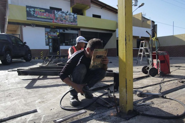 Workers repair the fence of a supermarket, after it was looted in Puerto Ordaz, Venezuela January 9, 2018. REUTERS/William Urdaneta
