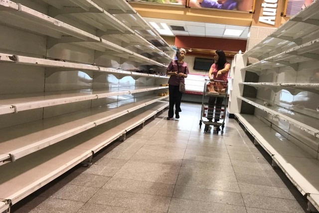 People walk past empty shelves at a supermarket in Caracas, Venezuela January 9, 2018. REUTERS/Marco Bello