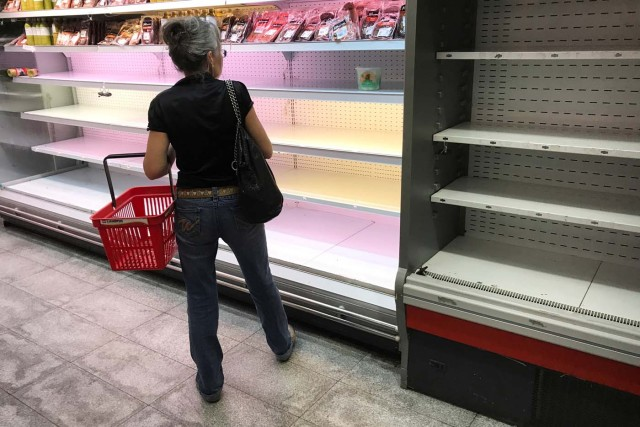 A woman looks at a partially empty refrigerator in a supermarket in Caracas, Venezuela January 9, 2018. REUTERS/Marco Bello