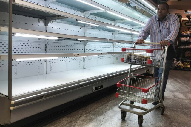 A man walks past an empty refrigerator at a supermarket in Caracas, Venezuela January 9, 2018. REUTERS/Marco Bello