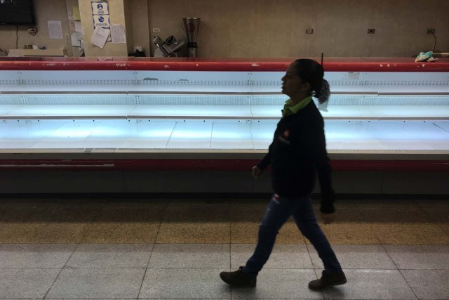A woman walks past an empty refrigerator at a supermarket in Caracas, Venezuela January 9, 2018. REUTERS/Marco Bello