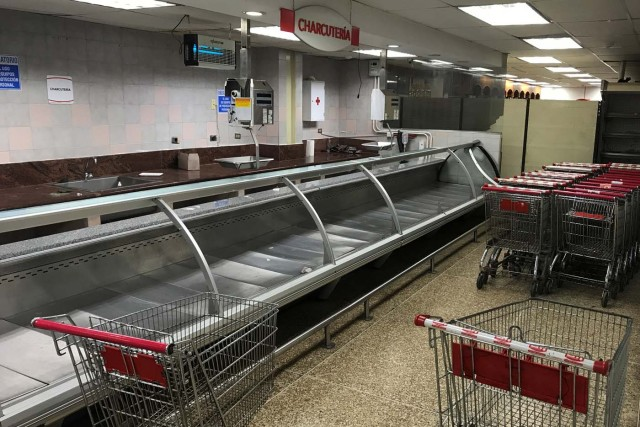 Stacked shopping carts are seen next to empty refrigerators at the deli area at a supermarket in Caracas, Venezuela January 10, 2018. REUTERS/Marco Bello