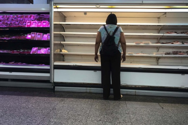 A woman stands in front of partially empty refrigerators at a supermarket in Caracas, Venezuela January 10, 2018. REUTERS/Marco Bello