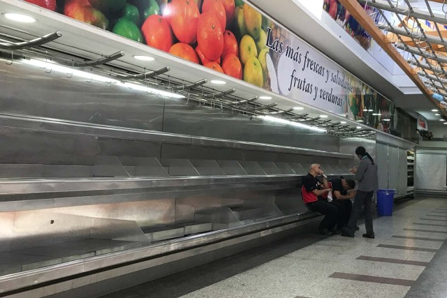 Workers sit on empty shelves at the fruit and vegetables area in a supermarket in Caracas, Venezuela January 10, 2018. REUTERS/Marco Bello