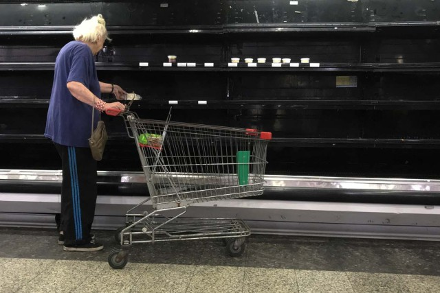 A woman selects goat cheese from partially empty refrigerators at a supermarket in Caracas, Venezuela January 10, 2018. REUTERS/Marco Bello