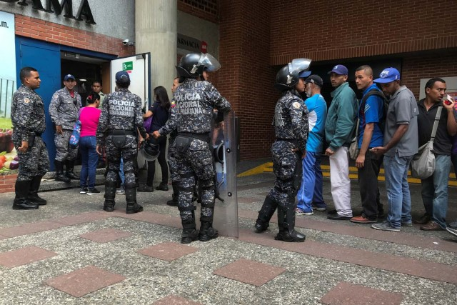 Police officers control the crowd as people line up to buy sugar, outside a supermarket in Caracas, Venezuela January 10, 2018. REUTERS/Marco Bello