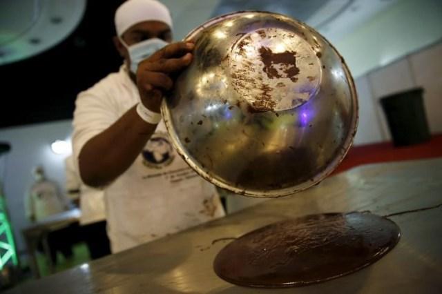 Imagen de archivo. Un artesano, vierte chocolate para hacer monedas en Caracas, Venezuela el 1 de octubre de 2015. REUTERS/Carlos Garcia Rawlins