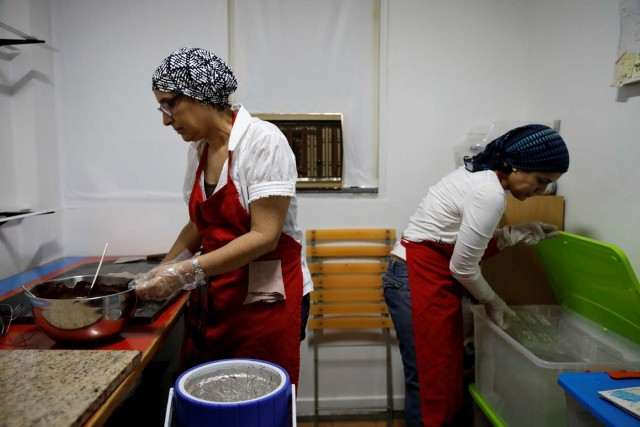 Adriana Pino (L) and Teresa Pino make chocolate bars at the +58 Cacao chocolate factory in Caracas, Venezuela October 6, 2017. Picture taken October 6, 2017. REUTERS/Carlos Garcia Rawlins
