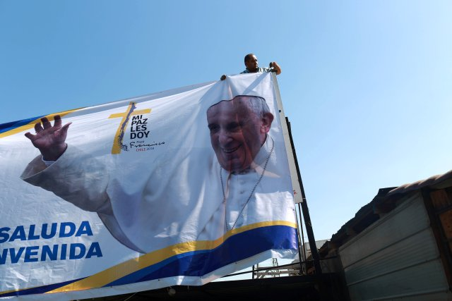 A man arranges a banner with an image of Pope Francis ahead of the papal visit, in Santiago, Chile January 10, 2018. Picture taken January 10, 2018. REUTERS/Pablo Sanhueza