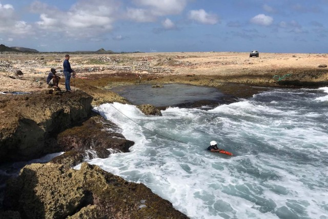 Police officers look for belongings and evidences at the shore where bodies of four people were found, after their boat broke apart several miles before reaching Curacao, according to a Venezuelan family member of one of the passengers on board who survived, near Willemstad, Curacao January 11, 2018. REUTERS/Umpi Welvaart
