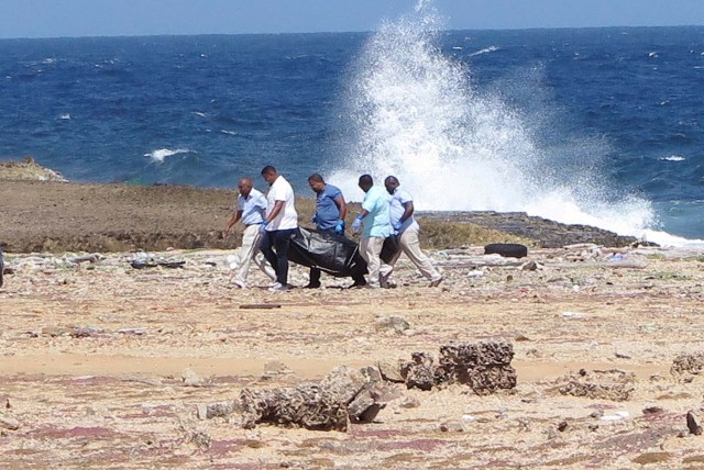 Forensic workers carry a bag containing the body of a person who was found at the shore, near Willemstad, Curacao January 10, 2018. Picture taken January 10, 2018. REUTERS/Umpi Welvaart