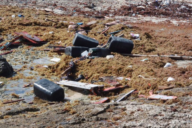 ATTENTION EDITORS - VISUALS COVERAGE OF SCENES OF INJURY OR DEATH Human bodies, plastic containers and pieces of wood are seen at the shore, after a boat broke apart, according to a Venezuelan relative of one of the passengers on board who survived, near Willemstad, Curacao January 10, 2018. Picture taken January 10, 2018. REUTERS/Umpi Welvaart TEMPLATE OUT