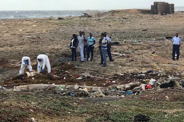 ATTENTION EDITORS - VISUALS COVERAGE OF SCENES OF INJURY OR DEATH Forensic workers take pictures and look at the body of a person who was found at the shore, near Willemstad, Curacao January 12, 2018. REUTERS/Umpi Welvaart TEMPLATE OUT