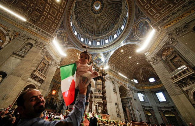 A migrant holds his child waving an Italian flag as Pope Francis leads a special mass to mark International Migrants Day in Saint Peter's Basilica at the Vatican January 14, 2018. REUTERS/Max Rossi