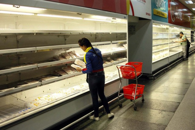 A woman selects deli from a partially empty refrigerator at a supermarket in San Cristobal, Venezuela January 16, 2018. REUTERS/Carlos Eduardo Ramirez