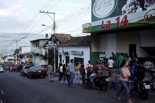 People line up outside a supermarket with its security shutters partially closed as a precaution against riots or lootings, in San Cristobal, Venezuela January 16, 2018. Picture taken January 16, 2018. REUTERS/Carlos Eduardo Ramirez