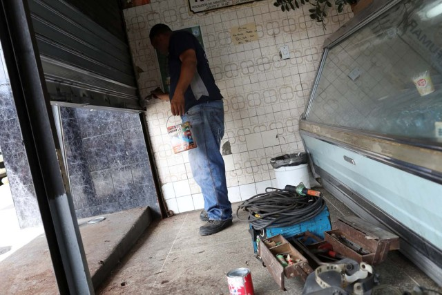 A worker paints a security shutter after repairing it at a bakery in Caracas, Venezuela January 16, 2018. Picture taken January 16, 2018. REUTERS/Marco Bello