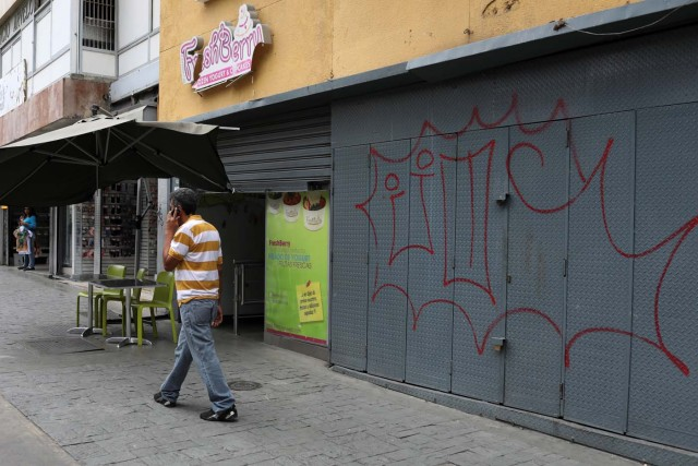 A man walks past reinforced security gates at a store in downtown Caracas, Venezuela January 16, 2018. Picture taken January 16, 2018. REUTERS/Marco Bello