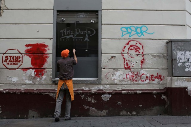 A worker closes the security shutter of a window at Arte Paris cafe in downtown Caracas, Venezuela January 16, 2018. Picture taken January 16, 2018. REUTERS/Marco Bello