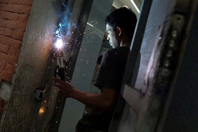 A worker welds a security gate at a shoe store in downtown Caracas, Venezuela January 16, 2018. Picture taken January 16, 2018. REUTERS/Marco Bello