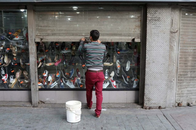 A worker closes the security shutter of a window display at a shoes store in downtown Caracas, Venezuela January 16, 2018. Picture taken January 16, 2018. REUTERS/Marco Bello