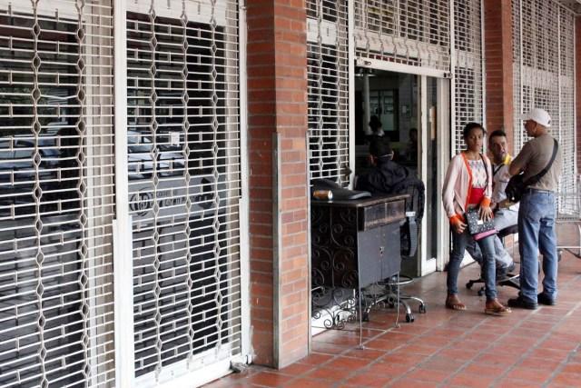 Una mujer sale de un supermercado con las rejas parcialmente cerradas como precaución contra disturbios o saqueos, en San Cristóbal, Venezuela, 16 de enero de 2018. REUTERS/Carlos Eduardo Ramirez