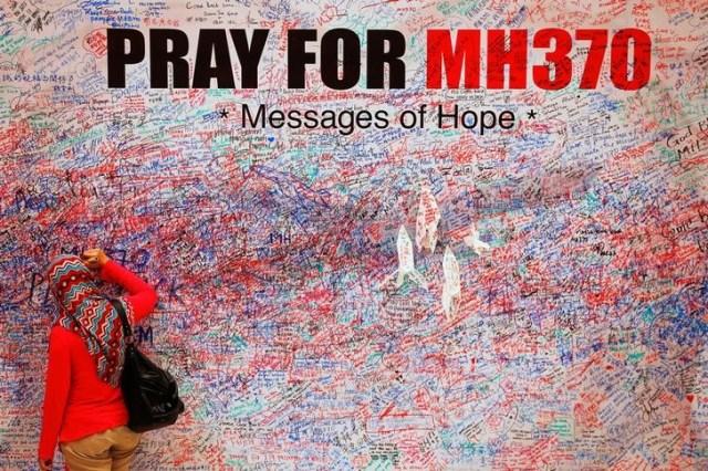 Una mujer deja un mensaje de apoyo y esperanza para los pasajeros del desaparecido Malaysia Airlines MH370 en el centro de Kuala Lumpur el 16 de marzo de 2014. REUTERS / Damir Sagolj / File Photo