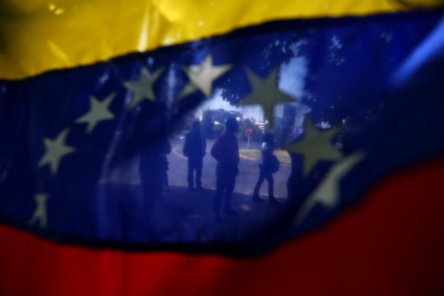 Demonstrators are seen through a Venezuelan flag during a rally against Venezuela's government as members of Lima Group nations meet in Santiago, Chile January 23, 2018. REUTERS/Ivan Alvarado