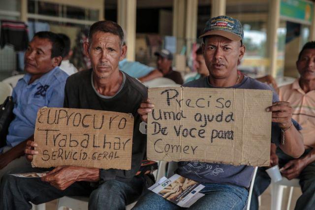 Inmigrantes venezolanos sostienen mensajes en búsqueda de trabajo en la ciudad brasileña de Boa Vista, estado de Roraima, octubre de 2017. Foto cortesía de la Oficina de Naciones Unidas contra la Droga y el Delito (ONUDC)