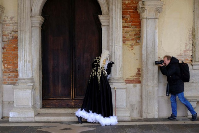 A masked reveller poses for a photographer during the Carnival in Venice, Italy January 28, 2018. REUTERS/Manuel Silvestri