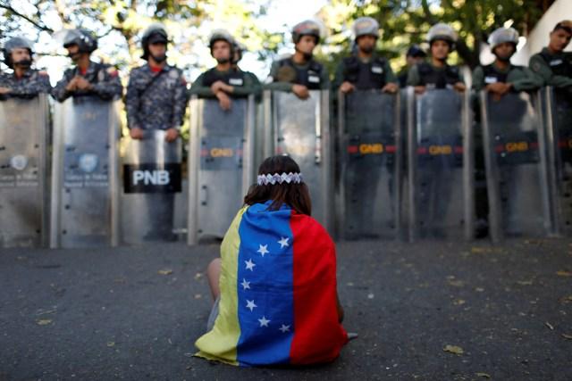 Una niña usa una bandera venezolana mientras las fuerzas de seguridad venezolanas bloquean el acceso a los partidarios de la oposición a la morgue principal de la ciudad, en Caracas, Venezuela. REUTERS/Marco Bello